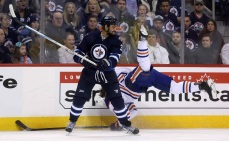 Winnipeg Jets' Dustin Byfuglien (33) hits Edmonton Oilers' Luke Gazdic (20) during second period NHL hockey action in Winnipeg, Monday, February 16, 2015. THE CANADIAN PRESS/Trevor Hagan