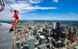 """A brave reporter leans over the edge of the catwalk during the media preview for the """"EdgeWalk"""" on the CN Tower in Toronto, July 27, 2011. Participants are strapped in to a harness that is attached to a guard rail while walking around the catwalk on the structure 1,168 feet above the ground."""