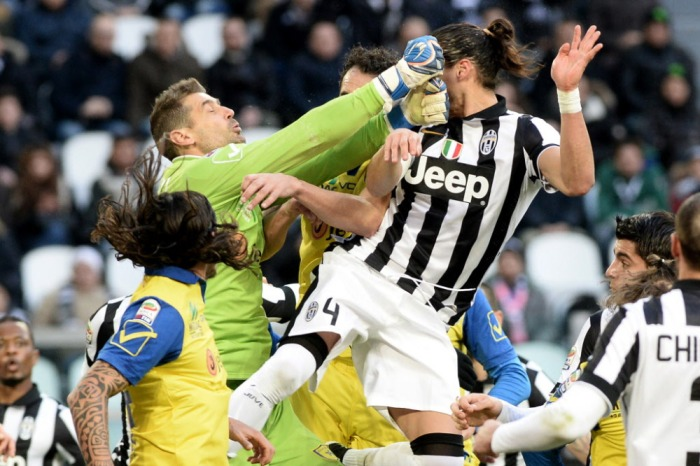 Chievo Verona goalkeeper Albano Bizzarri, top left, and Juventus' Martin Caceres collide as they go for the ball during a Serie A soccer match between Juventus and Chievo Verona at the Juventus stadium, in Turin, Italy, Sunday, Jan. 25, 2015. (AP Photo/Massimo Pinca) ORG XMIT: XMP105